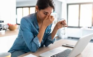 Woman at laptop looking like she's got a headache from trying to do program evaluation